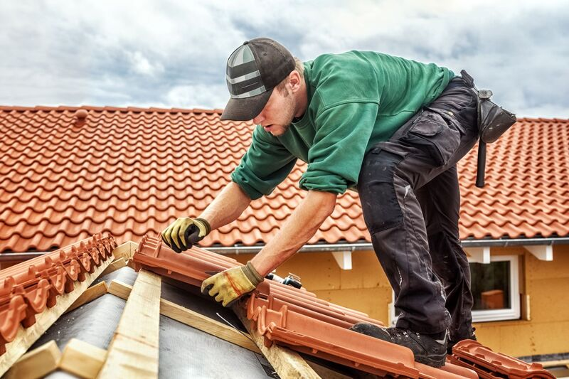 roofing contractor installing clay roof tiles