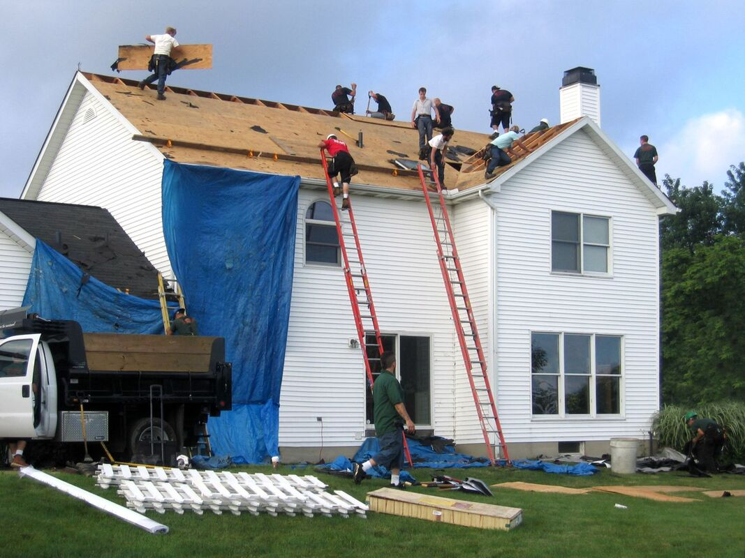Roofers replacing the roof on a home after storm damange